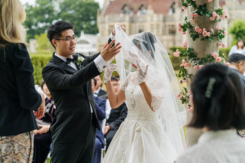 groom lifting veil at rhinefield house wedding