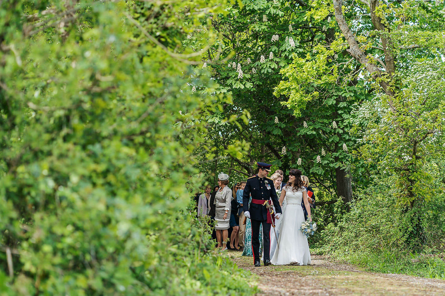 bride and groom walking with wedding guests
