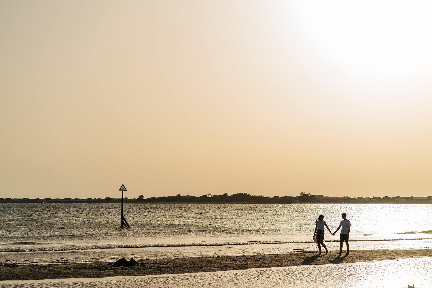 couple walking along west wittering beach