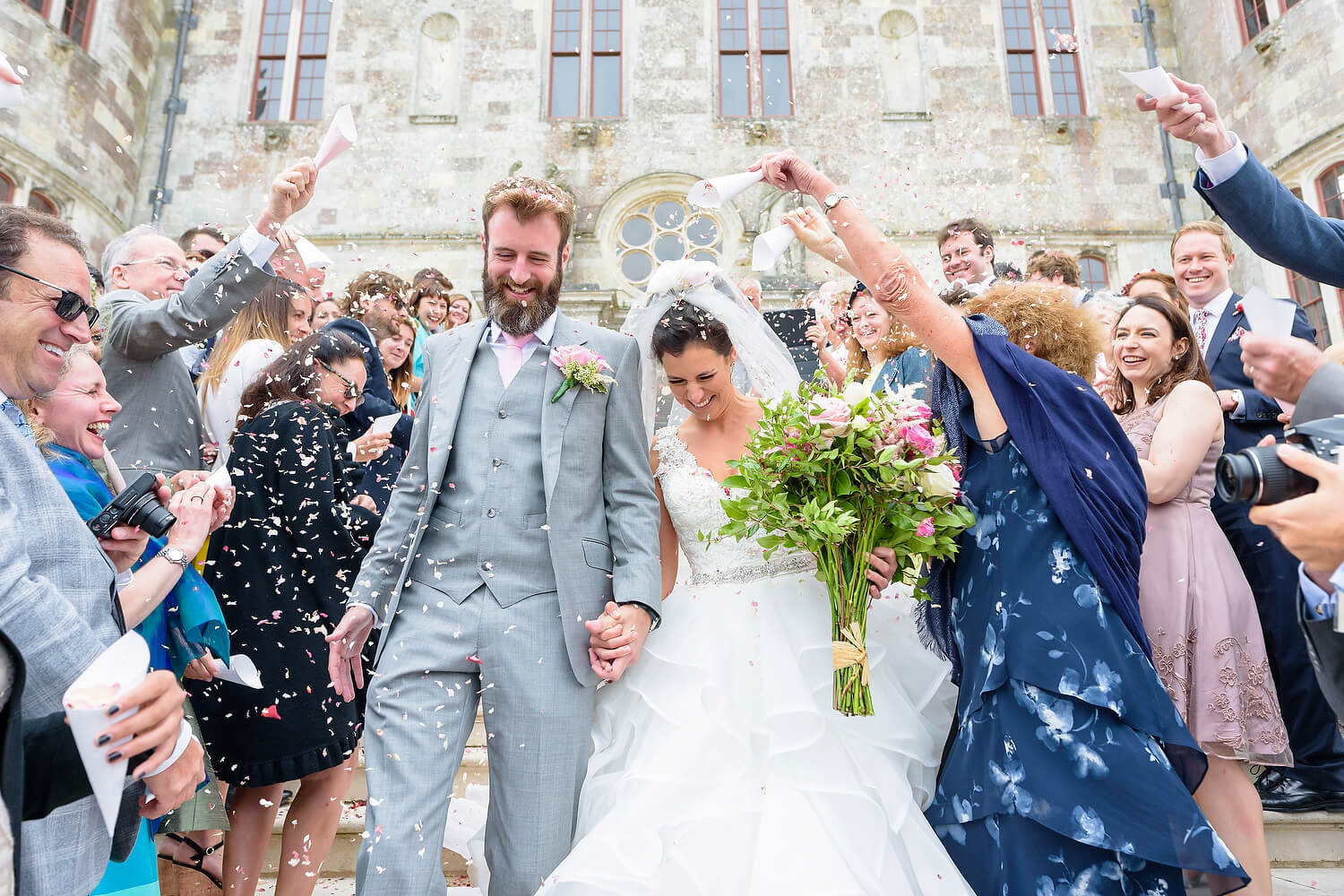bride and groom walking through confetti at lulworth castle