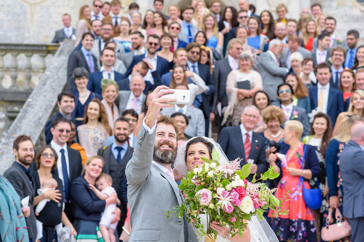 bride and groom selfie with wedding guests