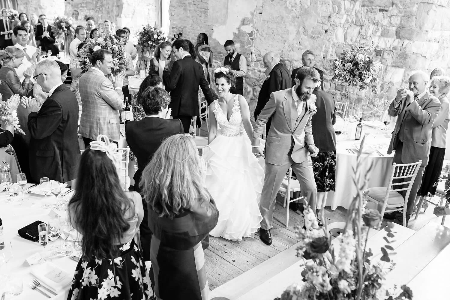 bride and groom walking into wedding at lulworth castle