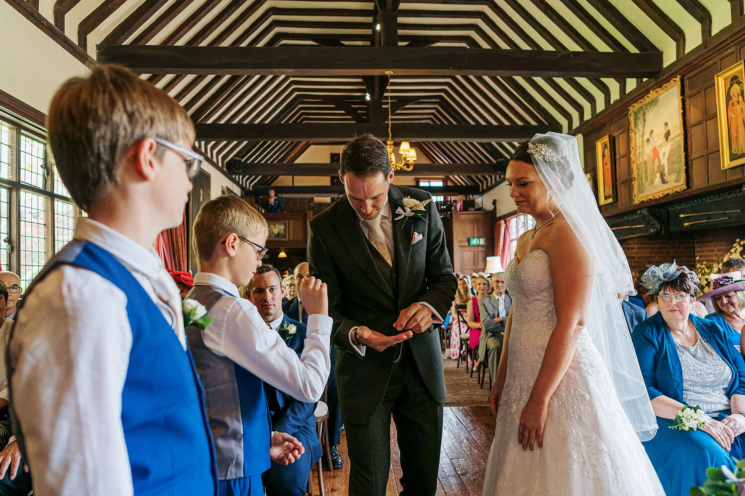 bride and groom exchanging rings at ramster hall