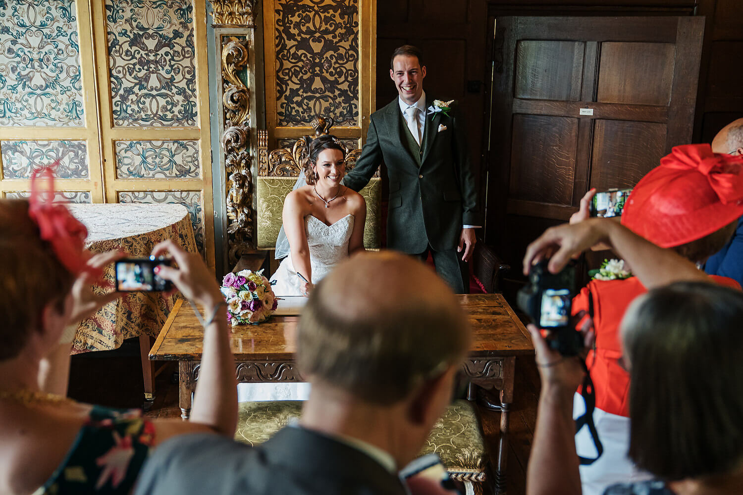 bride and groom signing register at ramster hall