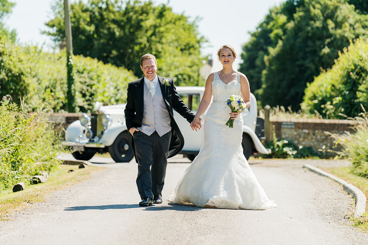 bride and groom with wedding car